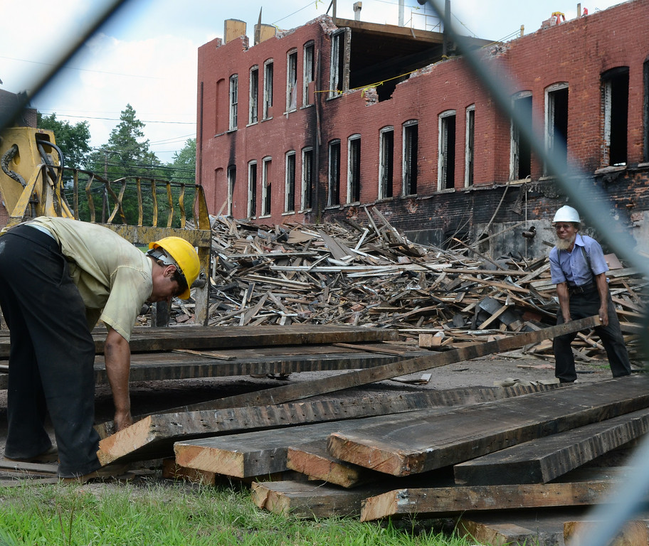 . Workers remove floor planks from the old Penn Pants Factory in Sellersville during demolition at the site on Tuesday July 22,2014.Photo by Mark C Psoras/The Reporter
