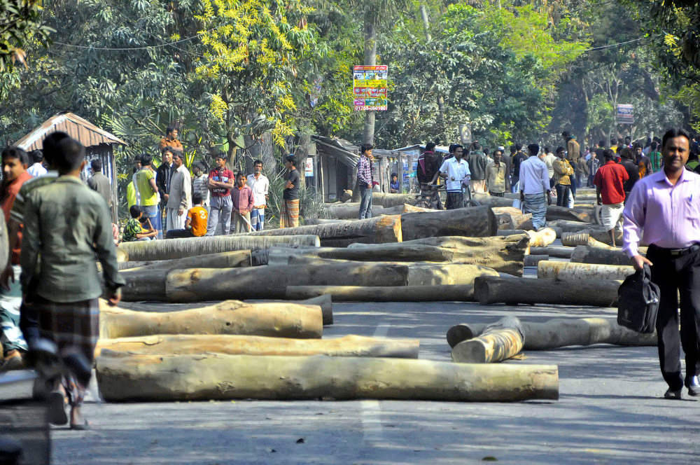 . Bangladeshi people walk past wooden logs placed on a road by activists of the country\'s largest Islamic party Jamaat-e-Islami to block traffic in Rajshahi, Bangladesh, Sunday, March 3, 2013. Authorities deployed soldiers in a northern Bangladeshi district on Sunday after Islamic party activists clashed with police, leaving five people dead during a nationwide general strike called to denounce war crimes trials. (AP Photo)