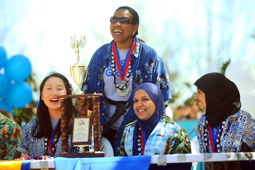 . Coach Stephanie Franklin shares a smile with Melissa Cheng, Neelem Sheikh, and Thasneem Syed (l-r) during a rally for El Camino Real Charter High School\'s Academic Decathlon team who won its seventh national title last week in Honolulu, Hawaii.(Andy Holzman/Los Angeles Daily News)