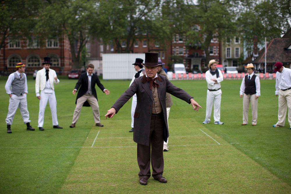. British author and former politician Jeffrey Archer gestures as he tries to help members of the media in organizing a posed photograph of the players before umpiring a Victorian-era costume themed cricket match on a wicket in Vincent Square, central London, Wednesday, May 29, 2013.  The two-over-a-side Victorian match was held Wednesday to mark the launch of the 150th anniversary edition of the Wisden Cricketers\' Almanac. (AP Photo/Matt Dunham)