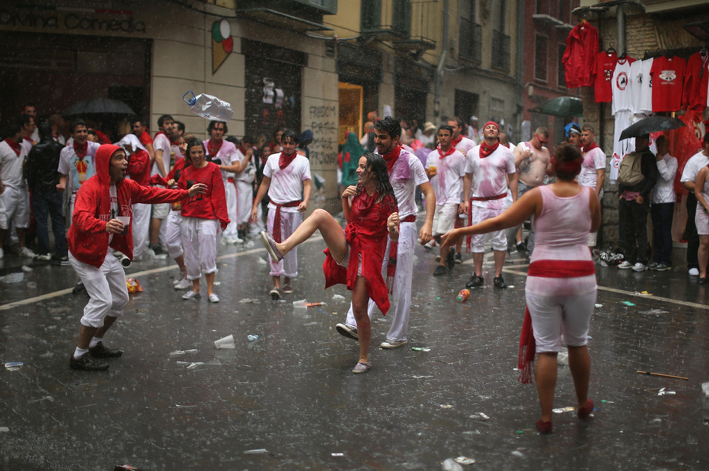 . Revellers dance in the rain after the opening and the firing of the  \'Chupinazo\' rocket which starts the 2014 Festival of the San Fermin Running of the Bulls on July 6, 2014 in Pamplona, Spain. The annual Fiesta de San Fermin, made famous by the 1926 novel of US writer Ernest Hemmingway entitled \'The Sun Also Rises\', involves the daily running of the bulls through the historic heart of Pamplona to the bull ring.  (Photo by Christopher Furlong/Getty Images)