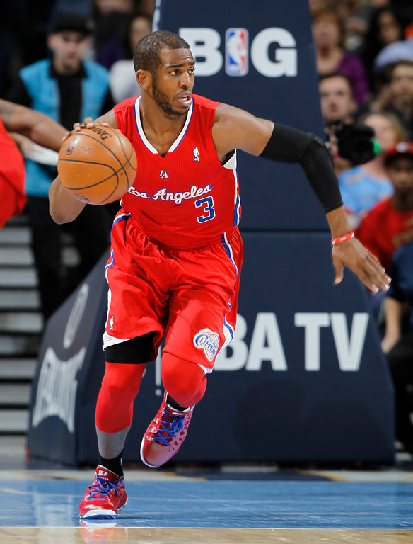 . Los Angeles Clippers guard Chris Paul picks up a loose ball against the Denver Nuggets in the first quarter of an NBA basketball game in Denver, Thursday, March 7, 2013. (AP Photo/David Zalubowski)