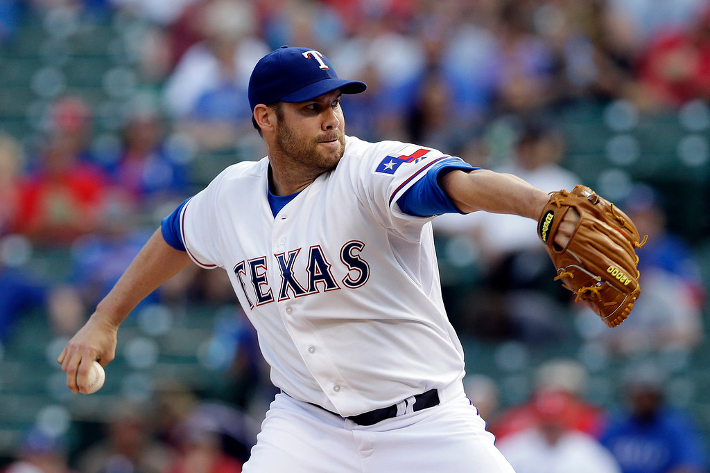 . Texas Rangers starting pitcher Colby Lewis winds up to deliver to the Colorado Rockies in the first inning of a baseball game, Wednesday, May 7, 2014, in Arlington, Texas. (AP Photo/Tony Gutierrez)