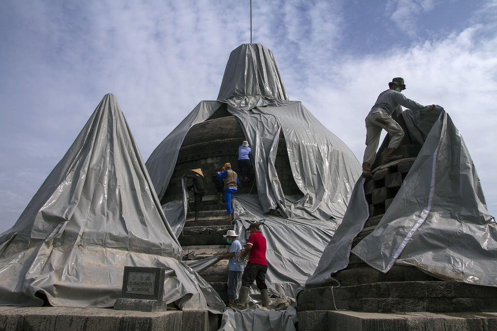 . Volunteers remove the protective covers from the stupas of the ancient Borobudur temple in Magelang, Central Java province on February 17, 2014 to begin the clean up of volcanic ash deposits following the eruption of Mount Kelud volcano. Borobudur, a Buddhist temple and Indonesia\'s national treasure built between the eighth and ninth century is located about 200 kilometers west of Kelud volcano, was blanketed by ash and temporarily closed to the public.  AFP PHOTO / SURYO WIBOWO/AFP/Getty Images