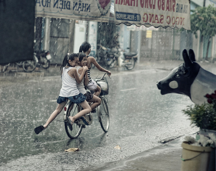 One of my more favorite photos from a recent trip to Vietnam. I was staying in a small city outside of Saigon and every day it would rain and pour.  I would go and take pictures of people doing their ordinary things in the flashes of heaviest rain.  These girls rode by and they began laughing as they saw my camera.  They had as much fun watching what I was doing, as I had watching and photographing what they were.  Several minutes later they rain stopped and they probably rode on and were completely dry 15 minutes after that.  It's an amazing place.