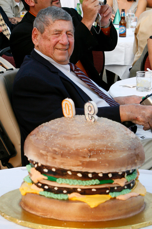 ". FILE - In this Aug. 21, 2008, file photo, Big Mac creator Michael ""Jim\"" Delligatti sits behind a Big Mac birthday cake at his 90th birthday party in Canonsburg, Pa. Delligatti, the Pittsburgh-area McDonald\'s franchisee who created the Big Mac in 1967, has died. He was 98. (AP Photo/Gene J. Puskar, File)"