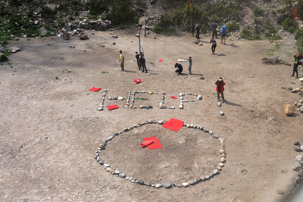 . Foreign trekkers and Nepalese guides are pictured alongside a \'HELP\' sign constructed with white stones, from an Indian Army helicopter at Machha Khola, in northern-central Gorkha district on April 29, 2015.  A giant \'HELP!\' spelled out with stones could be seen below from an Indian army chopper as a group of stranded foreign trekkers waved wildly for assistance in a remote area in the lush green Gorkha valley. The trekkers, a mix of Slovakians, Russian, German and French men and their Nepali guides, scrambled into the helicopter, lugging giant rucksacks. As the chopper took off, they all looked at each other with a sigh of relief, held hands and hugged one another as tears rolled down their faces.  AFP PHOTO / SAJJAD HUSSAIN /AFP/Getty Images
