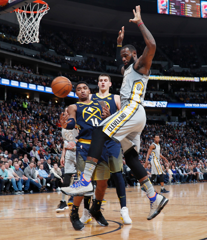 . Denver Nuggets guard Gary Harris, left, knocks the ball out of the hands of Cleveland Cavaliers forward LeBron James during the first half of an NBA basketball game Wednesday, March 7, 2018, in Denver. (AP Photo/David Zalubowski)