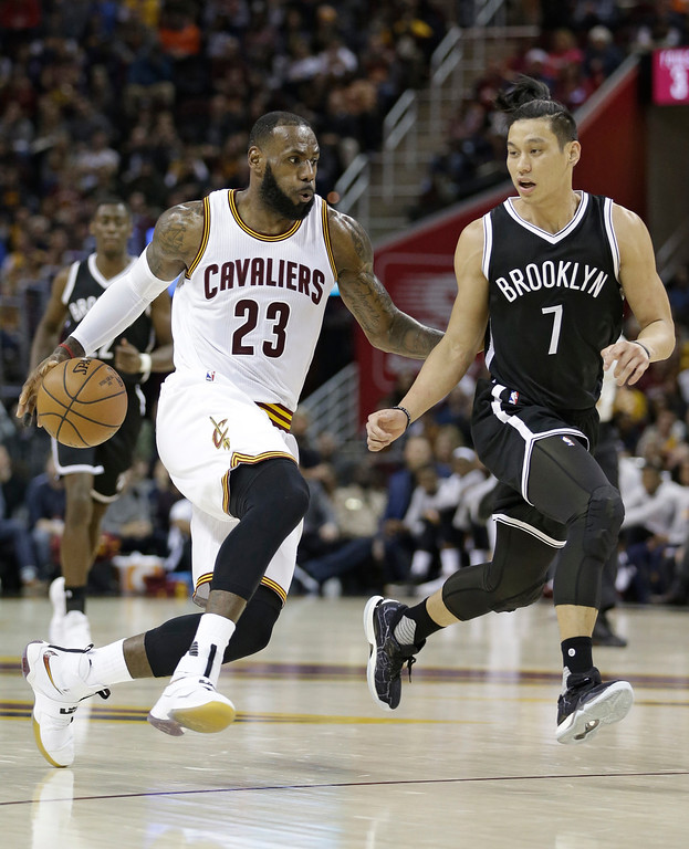 . Cleveland Cavaliers\' LeBron James (23) drives past Brooklyn Nets\' Jeremy Lin (7) in the first half of an NBA basketball game, Friday, Dec. 23, 2016, in Cleveland. (AP Photo/Tony Dejak)