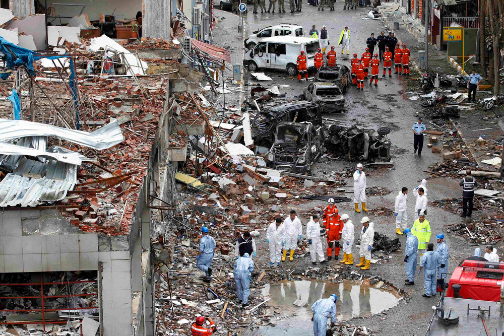 . Officials work on one of the sites of the twin car bomb attacks in the town of Reyhanli of Hatay province near the Turkish-Syrian border May 12, 2013. Twin car bombs killed 43 people and wounded many more in a Turkish town near the Syrian border on Saturday and the government said it suspected Syrian involvement. The bombing increased fears that Syria\'s civil war was dragging in neighboring states despite renewed diplomatic moves towards ending two years of fighting in which more than 70,000 people have been killed. The bombs ripped into crowded streets near Reyhanli\'s shopping district in the early afternoon, scattering concrete blocks and smashing cars in the town in Turkey\'s southern Hatay province, home to thousands of Syrian refugees. REUTERS/Umit Bektas