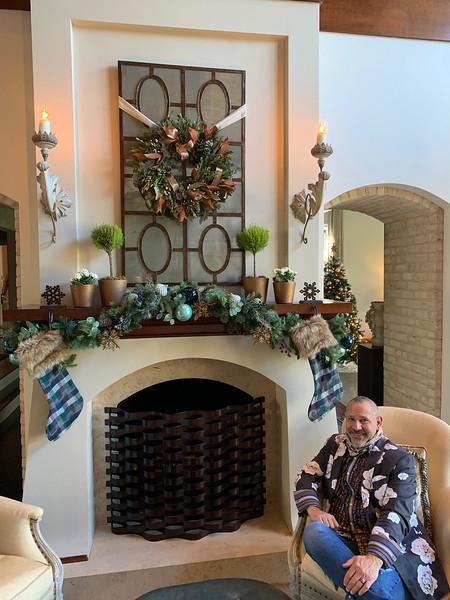 Jerry relaxes in front of the elaborately decorated fireplace of mixed greenery on the mantle, a magnolia wreath and, of course, plaid stockings with faux fur hung with care.