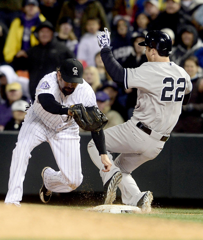 . New York Yankees\' Brennan Boesch (R) is called safe at first base after Colorado Rockies\' Todd Helton made the catch during their inter-league MLB baseball game in Denver, Colorado May 8, 2013. Boesch\'s single drove in Vernon Wells for the game winning run. REUTERS/Mark Leffingwell