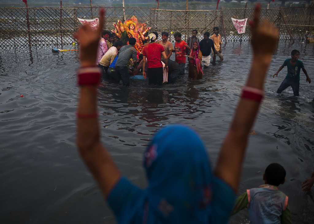 . An Indian Hindu devotee gestures as other devotees immerse an idol in  the Yamuna river as part of the Durga Puja festival in New Delhi on October 13, 2013. Durga Puja commemorates the slaying of demon king Mahishasur by goddess Durga, marking the triumph of good over evil.    Andrew Caballero-Reynolds/AFP/Getty Images