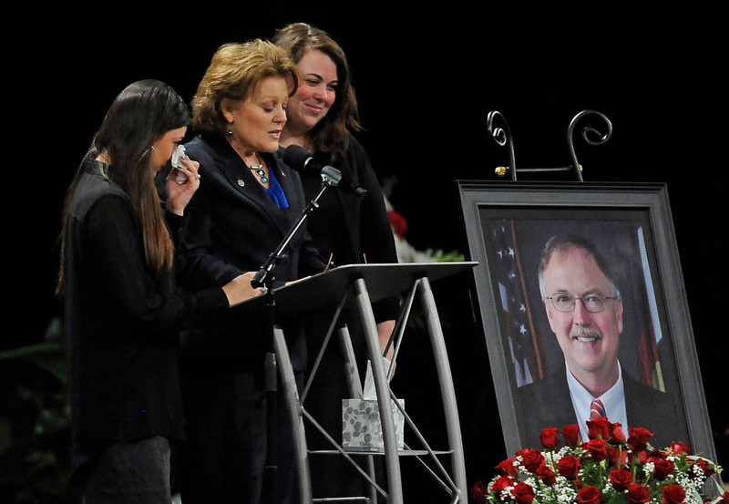 . Supported by her daughters Sara, left, and Rachel, Lisa Clements, the widow of Tom Clements, speaks at his public memorial at New Life Church in Colorado Springs, on Monday, March 25, 2013. Corrections officials and guards from as far away as Morocco are among the hundreds of people who turned out Monday to honor Clements, killed March 19 when he answered the door of his home in a wooded, rural area north of Colorado Springs. (AP Photo/The Gazette, Jerilee Bennett, Pool)