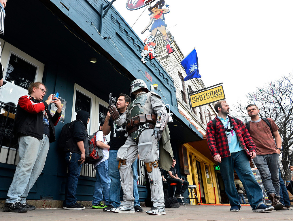 . A man dressed like Star Wars Boba Fett posses for pictures on sixth street on the first official day of South by Southwest in Austin, Texas, USA, 07 March 2014. South by Southwest (SXSW) Conferences and Festivals offer the unique convergence of original music, independent films, and emerging technologies.  EPA/LARRY W. SMITH