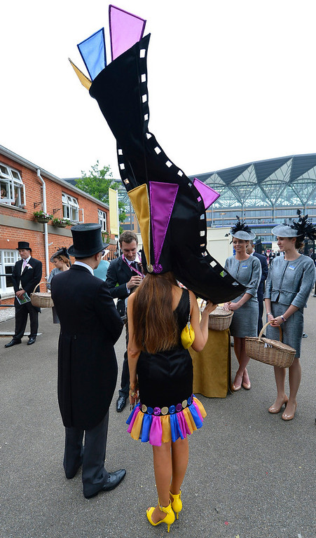 . Racecourse officials (R) monitoring dress code check racegoers as they arrive at the Royal Enclosure for ladies\' day at the Royal Ascot horse racing festival at Ascot, southern England, June 20, 2013. Big hats and fancy frocks are an integral part of Royal Ascot and organisers of Britain\'s glamorous racehorse meeting want to keep it that way by charging for fashion failures this year.   REUTERS/Toby Melville