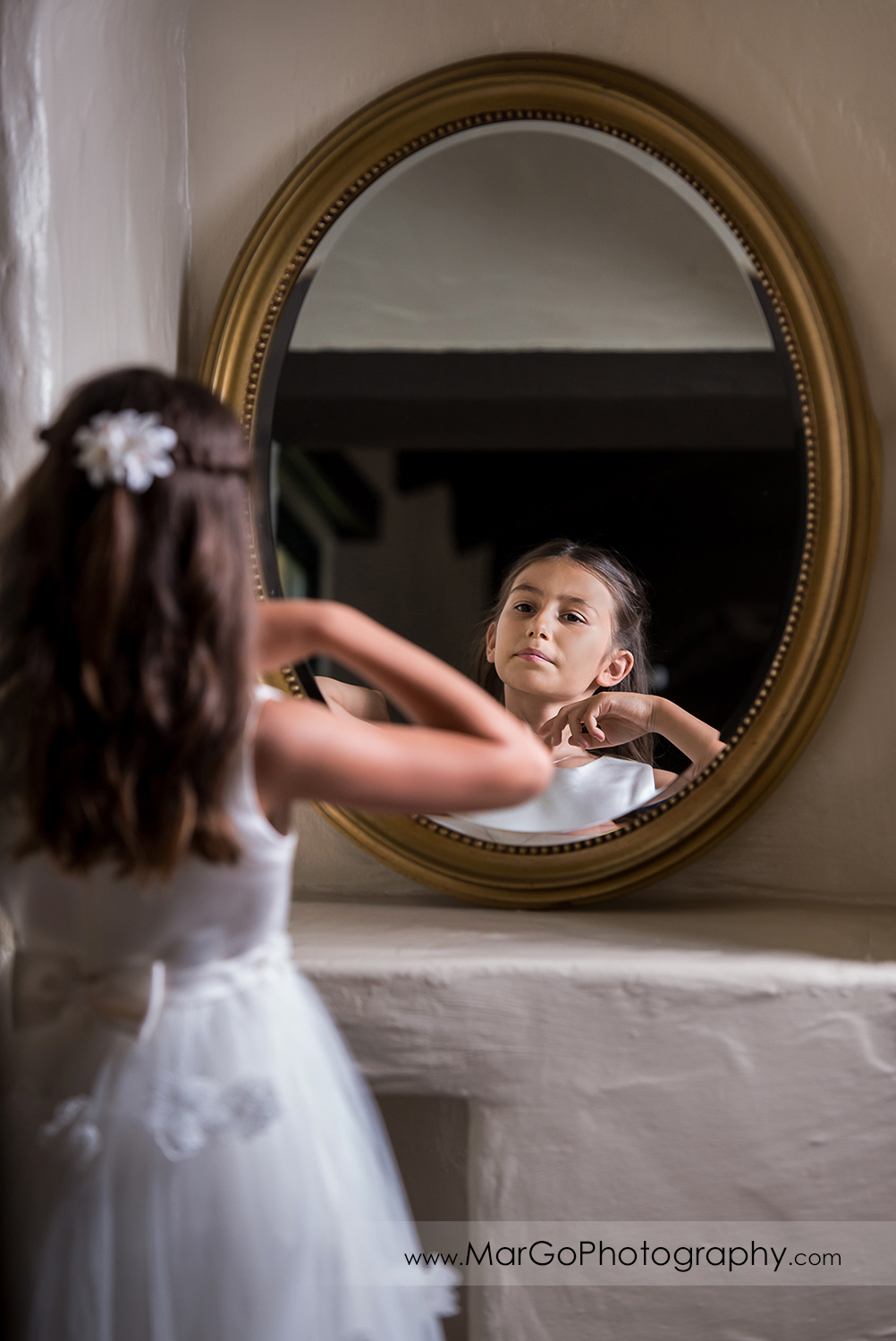 first communion girl in white dress looking in the mirror at Cafe Wisteria in Menlo Park