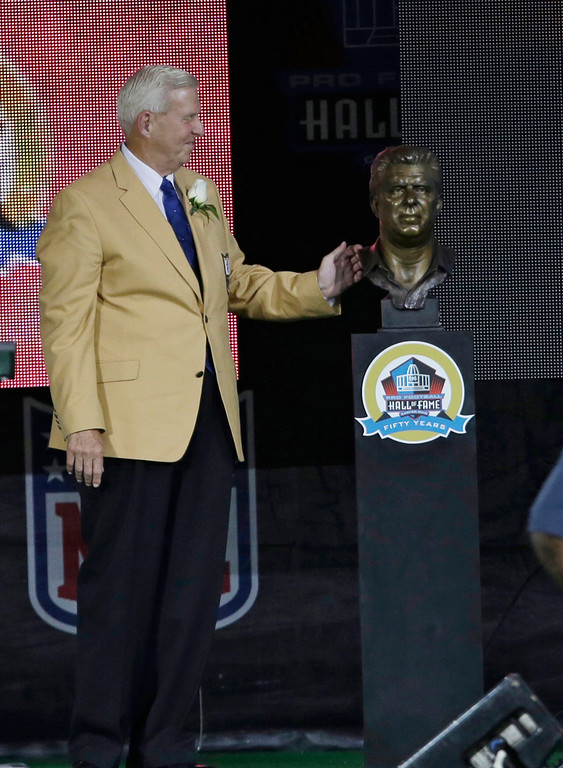 . Former NFL football head coach Bill Parcells looks at his bust after the unveiling during the induction ceremony at the Pro Football Hall of Fame Saturday, Aug. 3, 2013, in Canton, Ohio. (AP Photo/Tony Dejak)