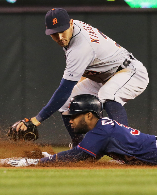 . Minnesota Twins\' Danny Santana, right, doubles off Detroit Tigers pitcher Rick Porcello as he beat the tag by Detroit Tigers second baseman Ian Kinsler in the fifth inning of a baseball game, Tuesday, Sept. 16, 2014, in Minneapolis. (AP Photo/Jim Mone)