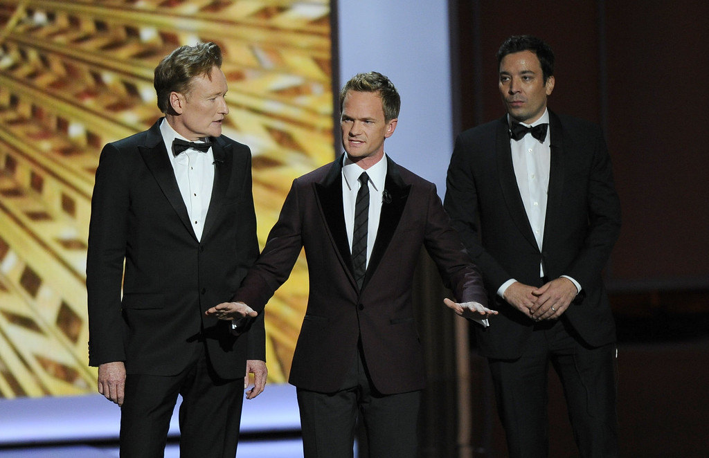 . Conan O\'Brien, from left, Neil Patrick Harris, and Jimmy Fallon speak onstage at the 65th Primetime Emmy Awards at Nokia Theatre on Sunday Sept. 22, 2013, in Los Angeles.  (Photo by Chris Pizzello/Invision/AP)