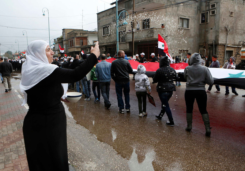 . A woman throws rice as other members of the Druze community holding a Syrian flag walk past during a rally marking Syria\'s Independence Day in the Druze village of Buqata on the Golan Heights April 17, 2013. Israel captured the Golan Heights from Syria in the 1967 Middle East war and annexed the territory in 1981, a move not recognized internationally. REUTERS/Baz Ratner