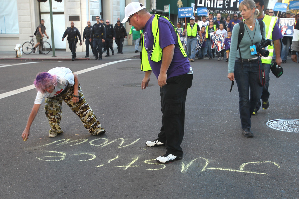 . A protestor makes a statement with a piece of chalk as ATU union member John O\'Connor disagrees with her writing on the ground during a peaceful march in support of BART workers in downtown Oakland, Calif., on Thursday, Aug. 1, 2013. (Ray Chavez/Bay Area News Group)