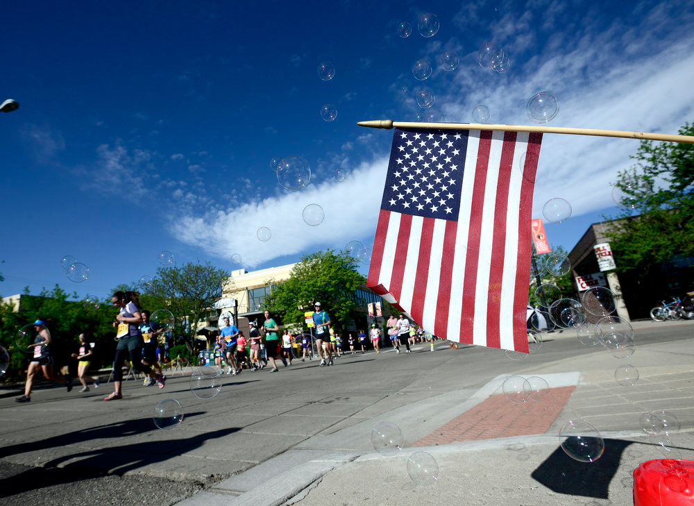 . An American Flag and bubble machine next to the course during the Bolder Boulder in Boulder, Colorado May 27, 2014.  DAILY CAMERA/ Mark Leffingwell