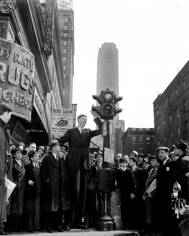 . Robert Wadlow, 18, of Alton, Ill., waits at a pedestrian traffic light as he is surrounded by a crowd in New York City, April 7, 1937.  Robert is standing with his father and manager, Harold Wadlow, left, with whom he is on a nationwide tour of schools, theaters and lecture halls.  Robert, who is 8 feet and 4 inches tall, will join the Ringling Brothers Circus for a six-week appearance.  (AP Photo)