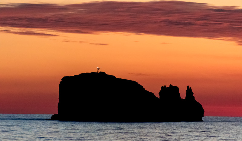Sunset colors in the sky behind a silhouetted island with a light on top that looks like a whale - , , , Mexico (MX)