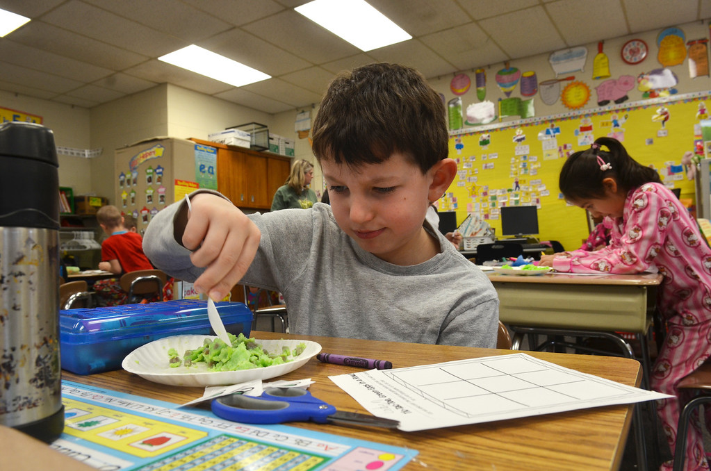 . First grader Caden Langeveld samples green eggs and ham in a classroom at Montgomery Elementary School.   The snack was served as part of Reading Week activity held annually to celebrate Dr. Seuss\'s birthday.    Friday, March 7, 2014.   Photo by Geoff Patton
