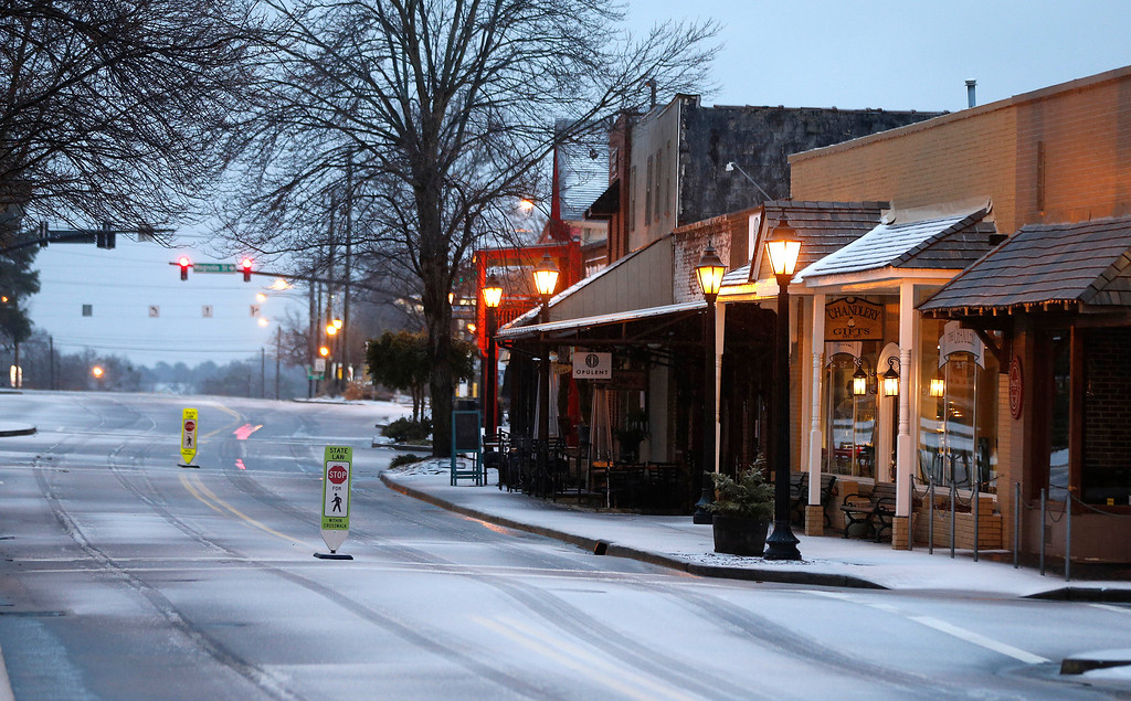 """. Snow and ice begin to cover Canton Street  in Roswell, Ga.,Wednesday, Feb. 12, 2014.  Across the South, winter-weary residents woke up Wednesday to a region encased in ice, snow and freezing rain, with forecasters warning that the worst of the potentially \""""catastrophic\"""" storm is yet to come. From Texas to the Carolinas and the South\'s business hub in Atlanta, roads were slick with ice, tens of thousands were without power, and a wintry mix fell in many areas.  (AP Photo/John Bazemore)"""