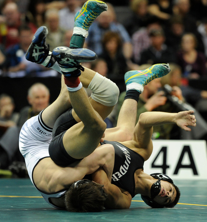 . DENVER, CO. - FEBRUARY 23: Pueblo South junior Marcus Martinez, left, flipped Discovery Canyon senior AJ Rees, right, during a class 4A, 120-pound championship match Saturday night. Rees prevailed to claim the state title. The CHSAA State Wrestling Tournament wrapped up, February 23, 2013, with final matches following the Parade of Champions at the Pepsi Center in downtown Denver. (Photo By Karl Gehring/The Denver Post)