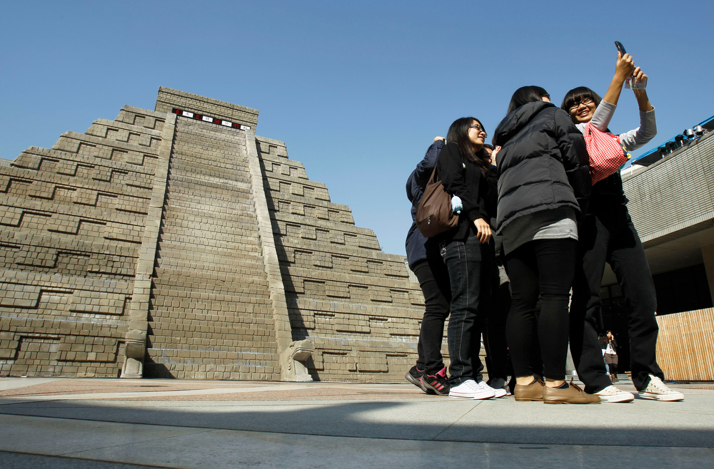 Description of . Students take pictures of themselves in front of a mock pyramid during the countdown to when many believe the Mayan people predicted the end of the world, Friday, Dec. 21, 2012, in Taichung, southern Taiwan. (AP Photo/Wally Santana)