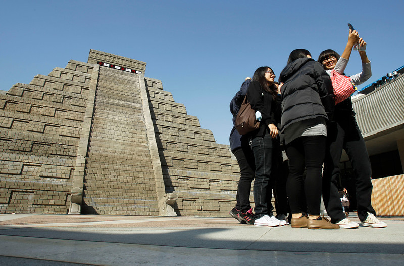 . Students take pictures of themselves in front of a mock pyramid during the countdown to when many believe the Mayan people predicted the end of the world, Friday, Dec. 21, 2012, in Taichung, southern Taiwan. (AP Photo/Wally Santana)