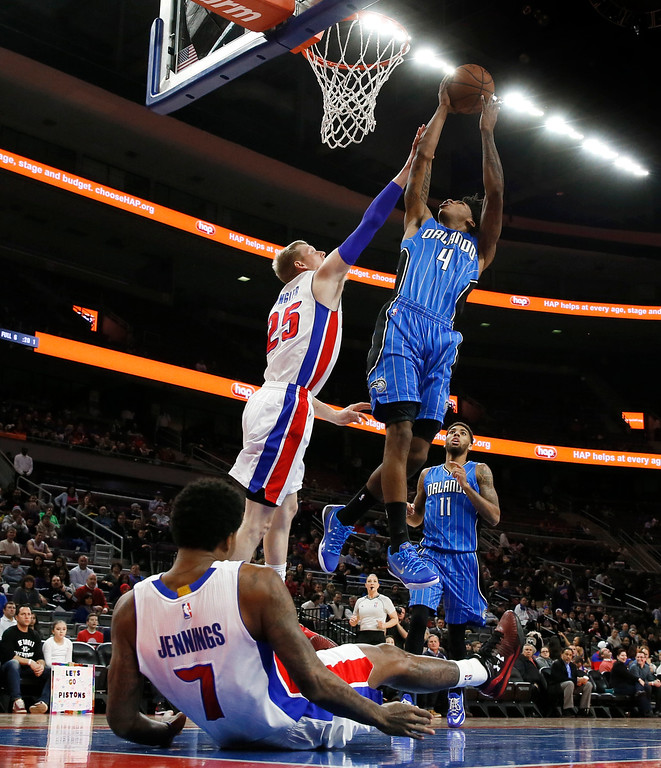 . Orlando Magic guard Elfrid Payton (4) shoots against Detroit Pistons forward Kyle Singler (25) in the first half of an NBA basketball game in Auburn Hills, Mich., Wednesday, Jan. 21, 2015. (AP Photo/Paul Sancya)