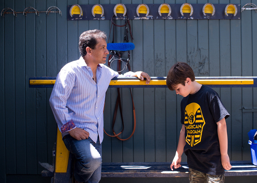 . Jockey Victor Espinoza and trainer Bob Baffert\'s 10-year-old son Bode wait for Triple Crown-winner American Pharoah to return home to Bob Baffert\'s barn at Santa Anita Thursday, June 18, 2015. American Pharoah and Espinoza broke a 37-year Triple Crown drought by winning the Kentucky Derby, Preakness and Belmont Stakes. (Photo by Sarah Reingewirtz/Pasadena Star-News)