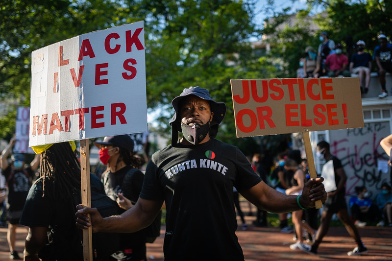 A protester holds signs in Lafayette Square in Washington, DC on May 31, 2020.