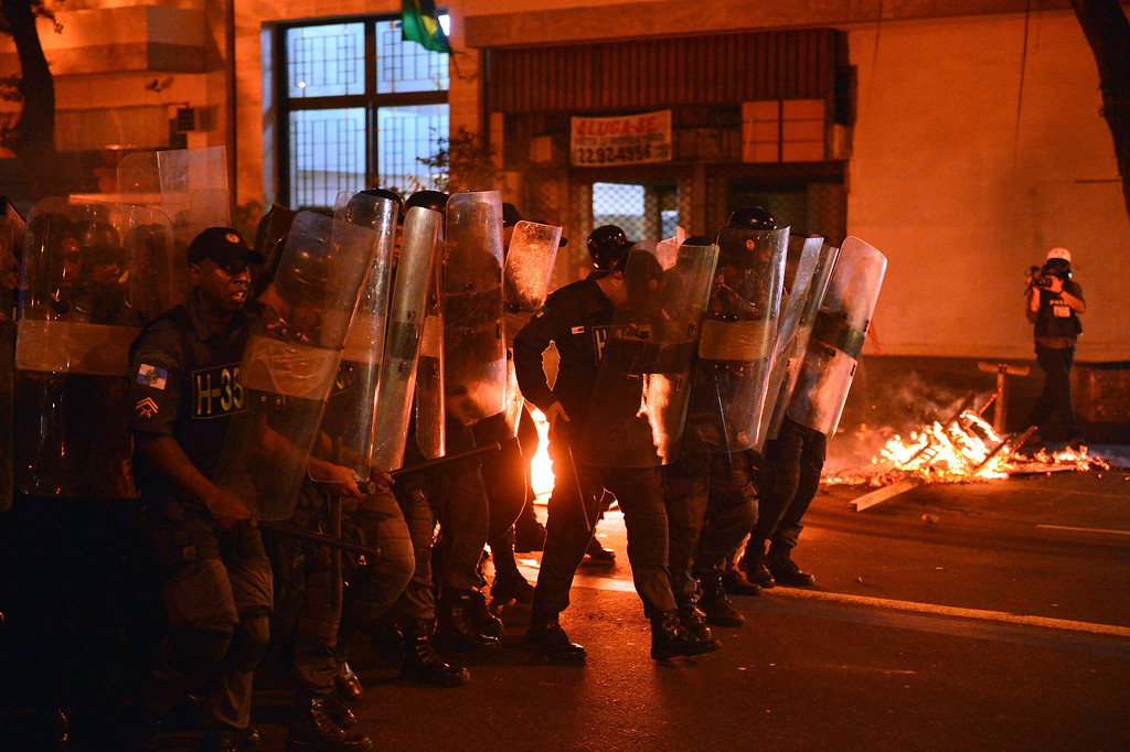 """. Policemen clash with demonstrators after a protest for the \""""Teachers\' day\"""", on October 15, 2013 in Rio de Janeiro, Brazil. AFP PHOTO / CHRISTOPHE SIMON/AFP/Getty Images"""