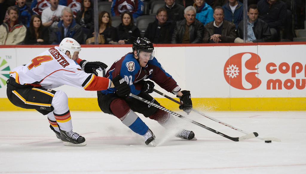 . DENVER, CO. - FEBRUARY 28: Gabriel Landeskog (92) of the Colorado Avalanche skates the puck in as he is shadowed by Jay Bouwmeester (4) of the Calgary Flames during the third period February 28, 2013 at Pepsi Center. The Colorado Avalanche defeated the Calgary Flames 5-4. (Photo By John Leyba/The Denver Post)
