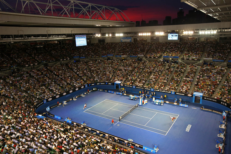 . With a backdrop of the city skyline in sunset, Tomas Berdych of the Czech Republic plays Stanislas Wawrinka of Switzerland during their semifinal at the Australian Open tennis championship in Melbourne, Australia, Thursday, Jan. 23, 2014.(AP Photo/Eugene Hoshiko)