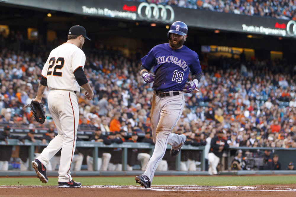 . Charlie Blackmon #19 of the Colorado Rockies scores a run past Jake Peavy #22 of the San Francisco Giants during the first inning at AT&T Park on August 25, 2014 in San Francisco, California.  (Photo by Jason O. Watson/Getty Images)