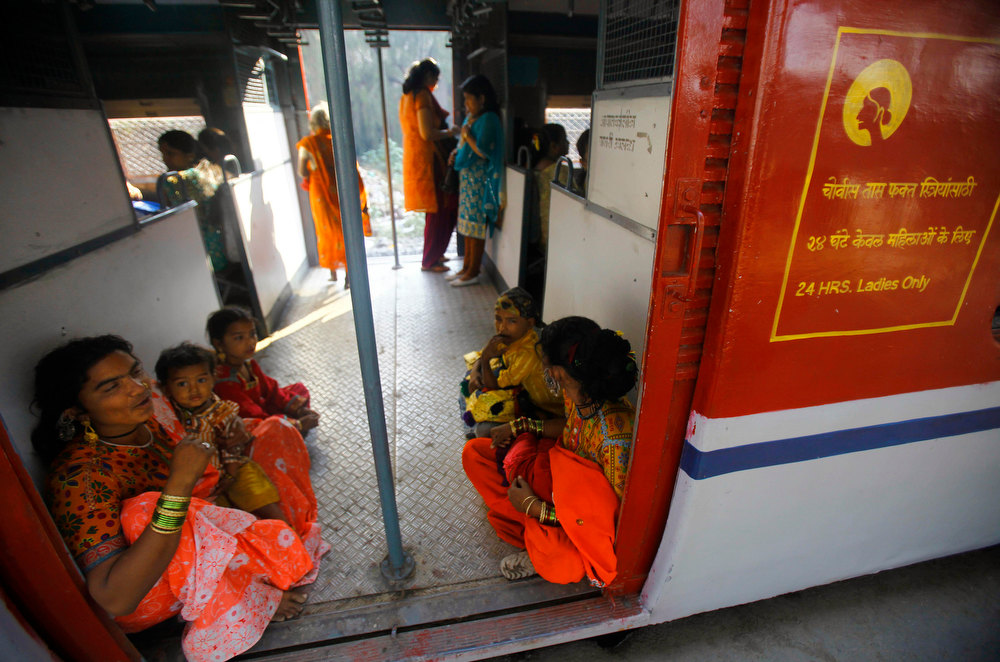 Description of . Indian women sit near the foot board of a train as they travel in the women's compartment early morning in Mumbai, India, Thursday, Jan. 10, 2013. Five men have been charged with attacking the 23-year-old woman and a male friend on a bus as it was driven through the streets of India's capital. The woman was raped and assaulted with a metal bar on Dec. 16, 2012 and eventually died of her injuries. The case has sparked protests across India by women and men who say India's legal system doesn't do enough to prevent attacks on women. (AP Photo/Rafiq Maqbool)