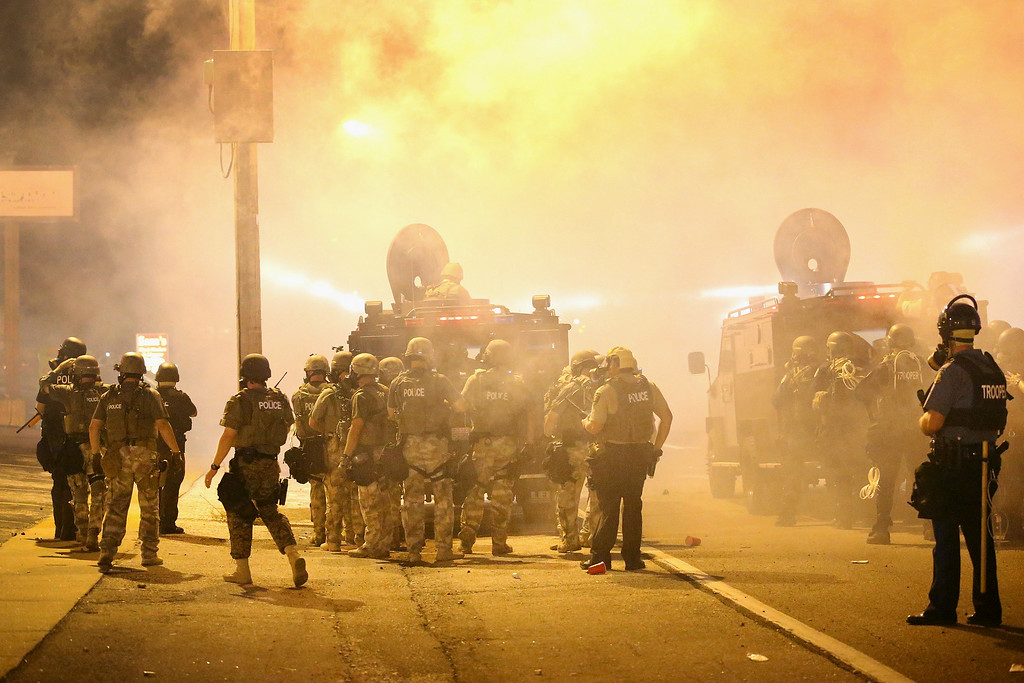 . Police advance through a cloud of tear gas toward demonstrators protesting the killing of teenager Michael Brown on August 17, 2014 in Ferguson, Missouri. Police shot smoke and tear gas into the crowd of several hundred as they advanced near the police command center which has been set up in a shopping mall parking lot. Brown was shot and killed by a Ferguson police officer on August 9. Despite the Brown family\'s continued call for peaceful demonstrations, violent protests have erupted nearly every night in Ferguson since his death.  (Photo by Scott Olson/Getty Images)