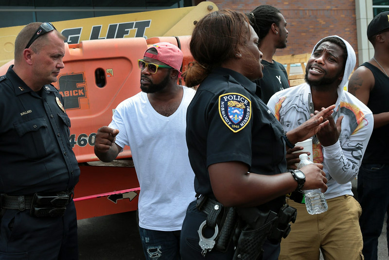 . Jamahl Spence, right, pleads his case with a Normandy police officer in front of the Ferguson, Mo. police station on Sunday, Aug. 10, 2014, one day after a Ferguson officer shot and killed Michael Brown. (AP Photo/St. Louis Post-Dispatch, Robert Cohen)
