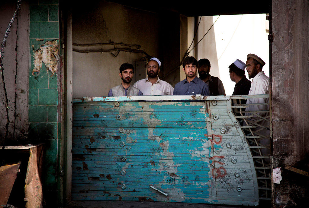 . Afghan men peer through the gate of their house at the scene where a suicide car bomber attacked a NATO convoy in Kabul, Afghanistan, Thursday, May 16, 2013.  (AP Photo/Anja Niedringhaus)