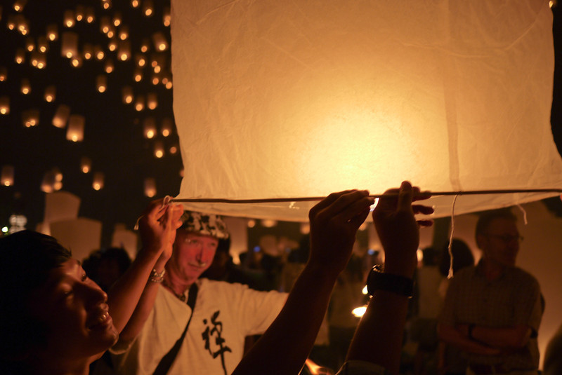 Captivated by the flame as the lantern fills with hot air during Loy Krathong in Chiang Mai, Thailand