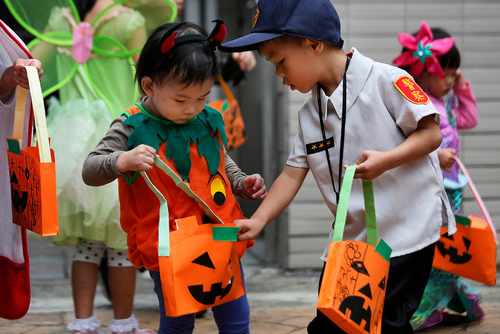 . Children in costume check each other\'s candy collection while celebrating Halloween in a local neighborhood of Taipei, Taiwan, Thursday, Oct. 31, 2013. (AP Photo/Wally Santana)