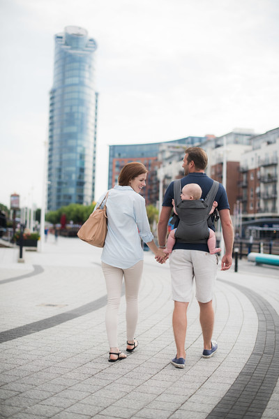 Izmi_Baby_Carrier_Mid_Grey_Lifestyle_Back_Carry_Mum_And_Dad_Walking_In_City_Wide_Angle.jpg