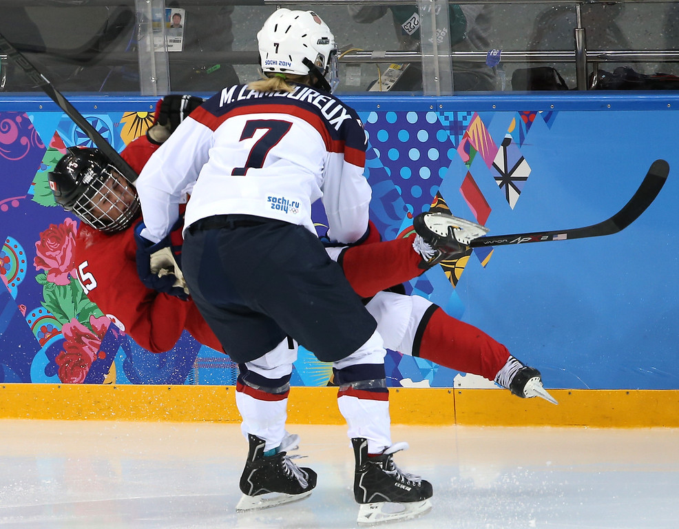 . Melodie Daoust #15 of Canada falls after colliding with Monique Lamoureux #7 of the United States during the Women\'s Ice Hockey Preliminary Round Group A game on day five of the Sochi 2014 Winter Olympics at Shayba Arena on February 12, 2014 in Sochi, Russia.  (Photo by Bruce Bennett/Getty Images)