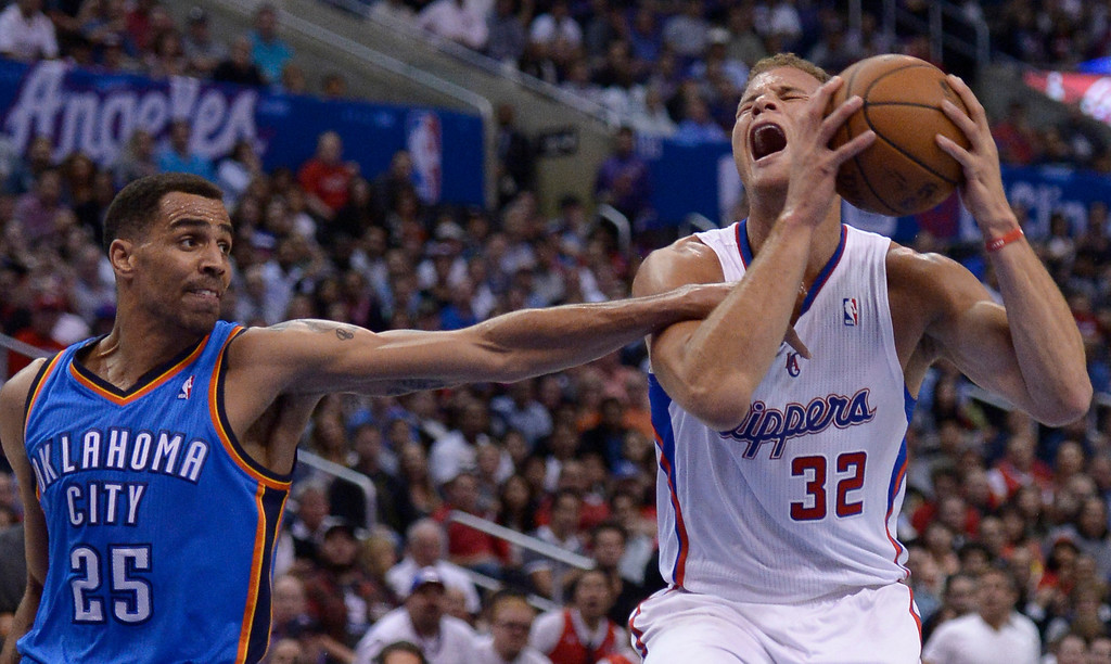 . Thunder#25 Thabo Sefolosha reaches in an fouls Clippers#32 Blake Griffin in the first quarter. The Los Angeles Clippers played the Oklahoma City Thunder in a regular season game at Staples Center in Los Angeles, CA. 4/9/2014(Photo by John McCoy / Los Angeles Daily News)